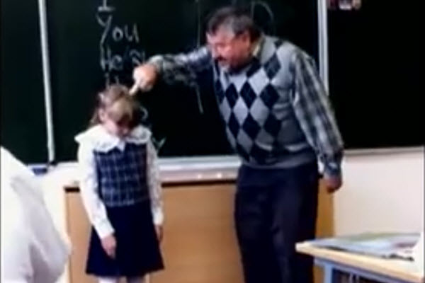 An English teacher in Russia angrily pokes a little Russian schoolgirl's head with his middle finger during a lesson.