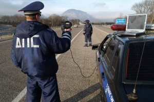 A traffic officer performs radar checks on oncoming cars