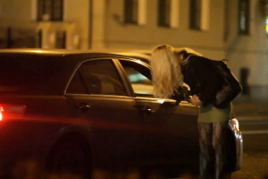 A girl leans into the window of a car that approached her.