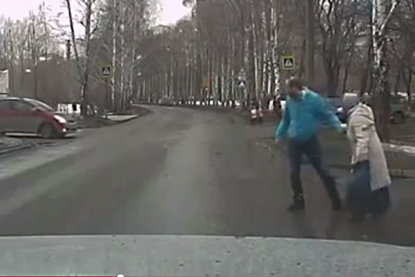 A kind man helps an older lady cross the road
